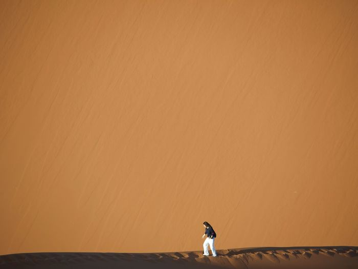 Woman walking on sand at desert