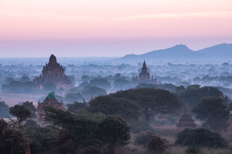 Temples Against Sky During Sunrise In Foggy Weather