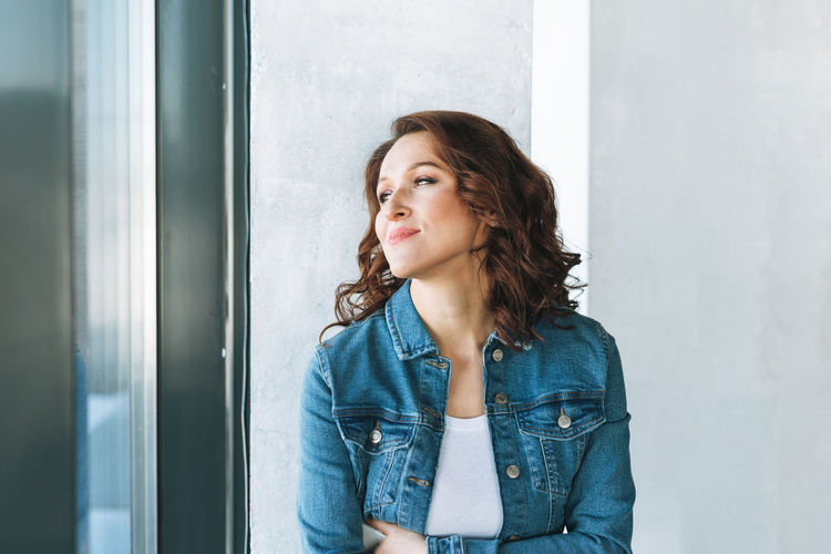 Portrait of smiling charming young woman in jeans jacket near window in modern building