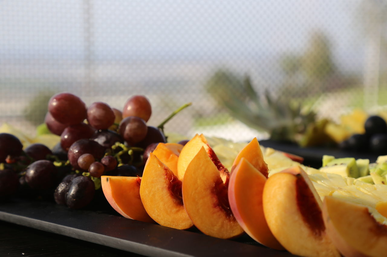 Close-Up Of Peaches And Grapes In Plate On Table