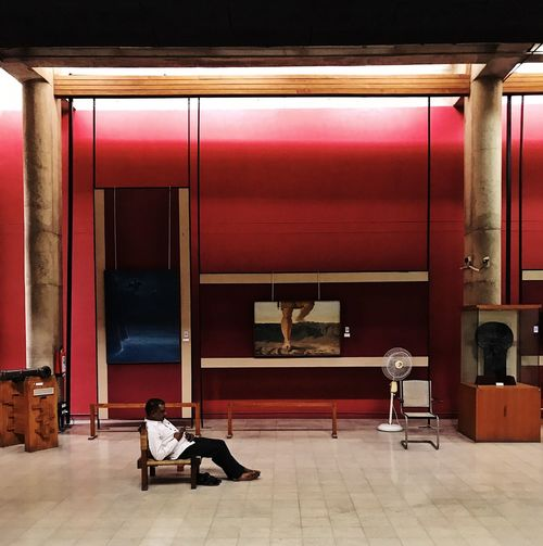 Architecture Chandigarh India Modern Architecture Museum Of Modern Art Paintings Brutalism Chair Concrete Illuminated Indoors  Interior Museum Pink Color Real People Red Relaxation Representation Seat Sitting Tiled Floor Wall - Building Feature