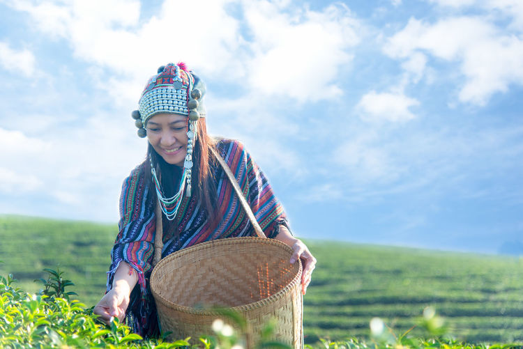Woman harvesting tea crops against sky