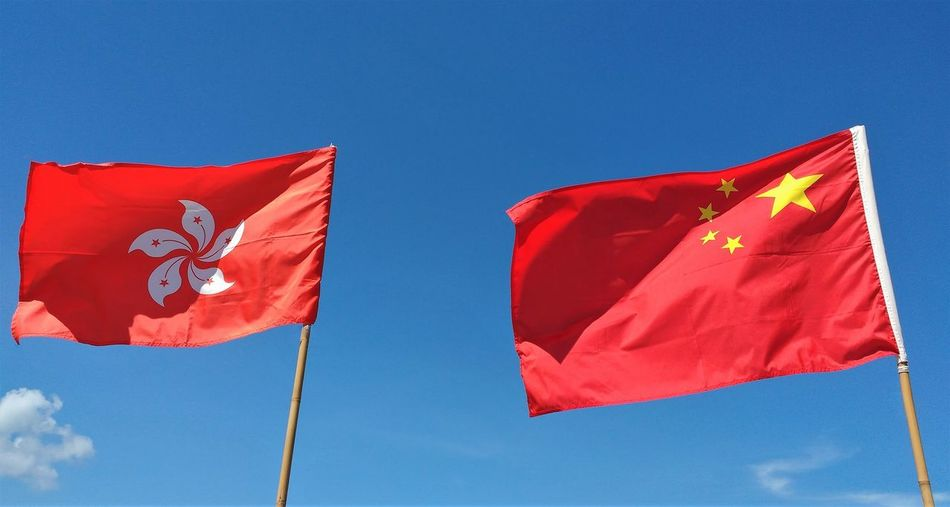 Low angle view of red flags against blue sky