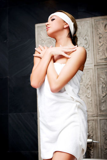 Woman Wrapped In Towel While Standing At Bathroom