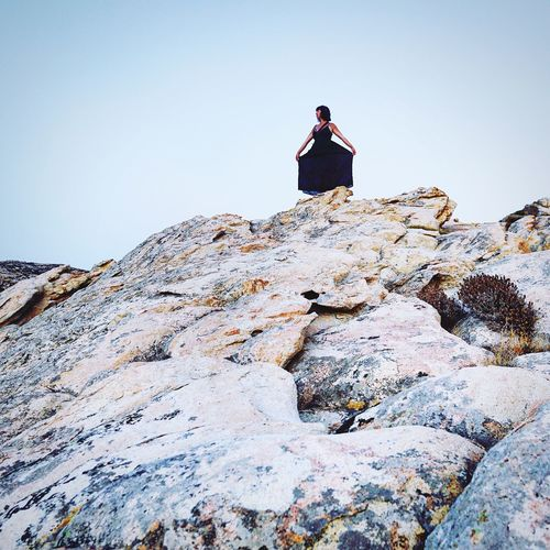 Low angle view of person standing on rock