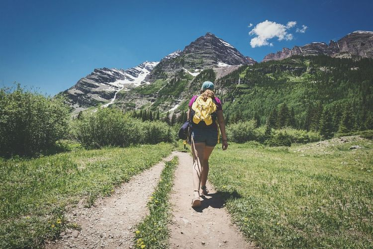 Full Length Rear View Of Woman With Backpack Walking On Dirt Road Against Mountains