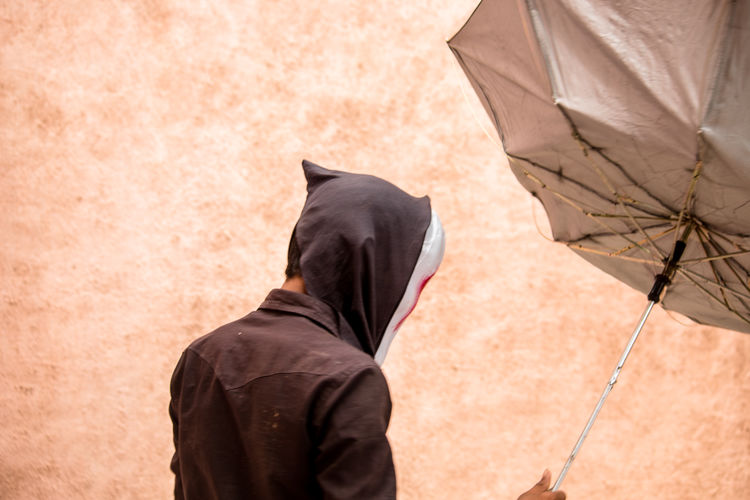 Man wearing mask with umbrella against wall