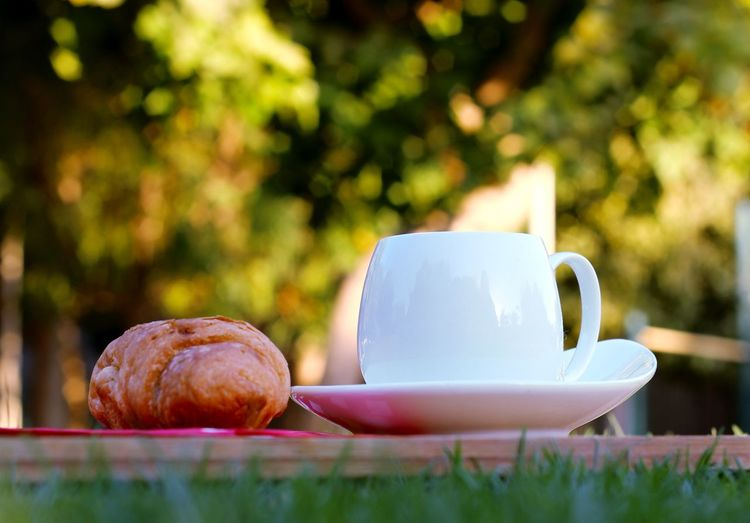 Close-Up Of Croissant And Tea Cup On Cutting Board