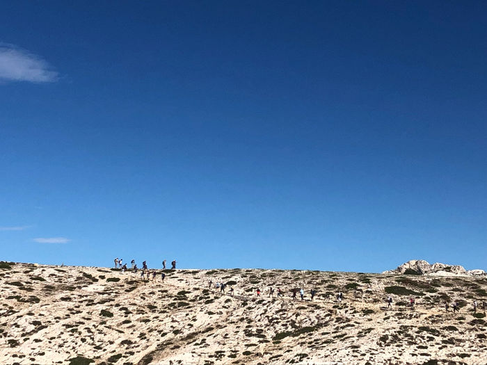 People on arid landscape against clear blue sky