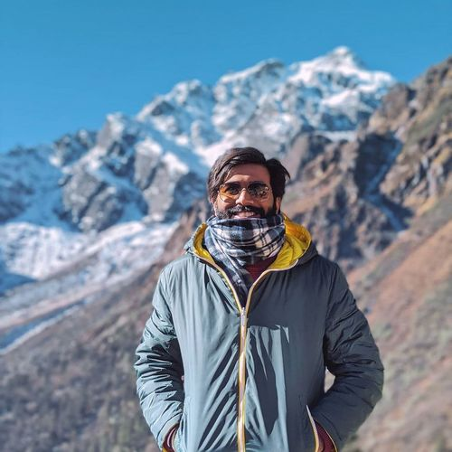 Portrait of man standing on snowcapped mountain