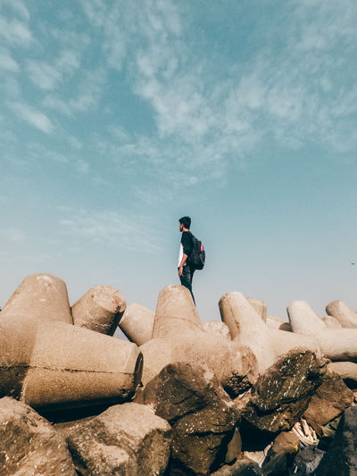 Low angle view of man standing on tetrapod against sky