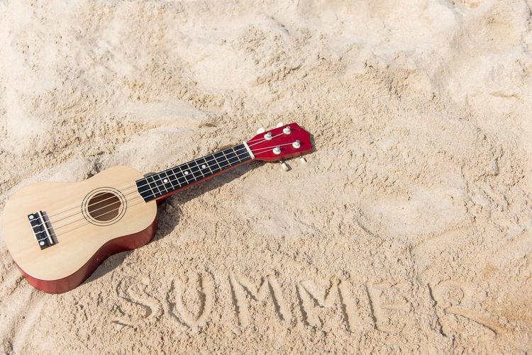 High angle view of guitar on sand