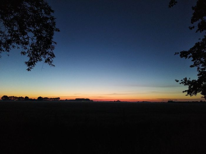 Scenic view of silhouette field against clear sky at sunset