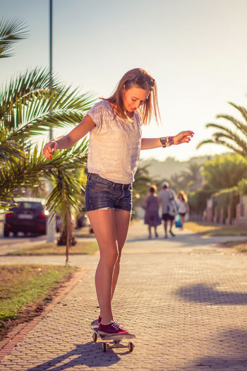 Full length of young woman standing on palm tree in city