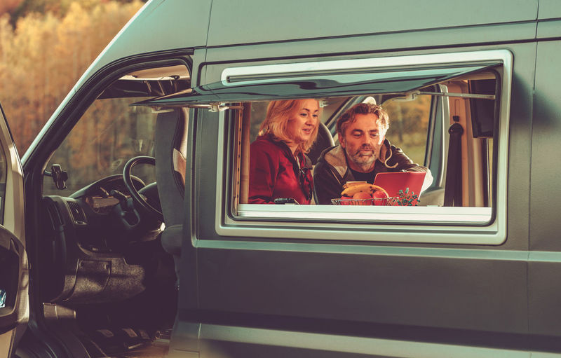 Smiling couple watching movie while sitting in motor home