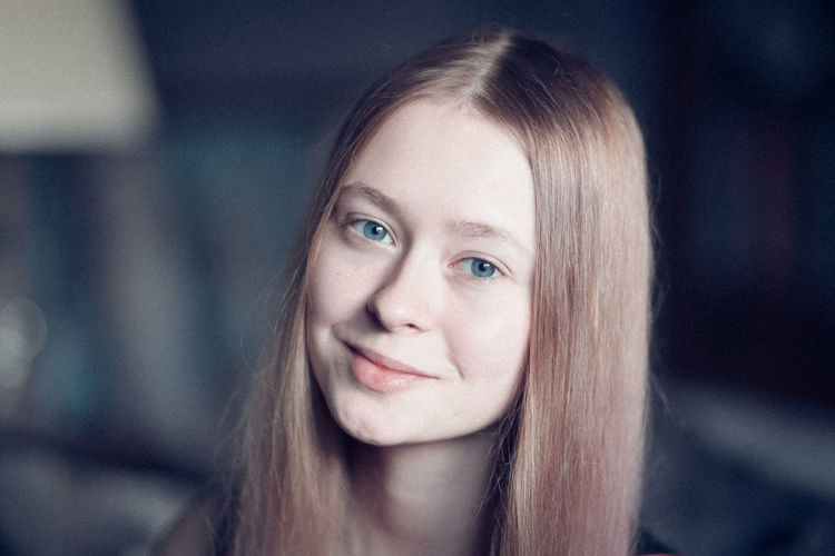 Close-up portrait of smiling teenage girl at home