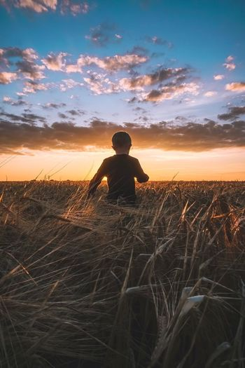 Boy walking on field against sky during sunset