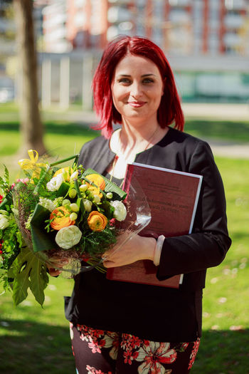 Portrait of smiling woman holding flower bouquet and book while standing in park