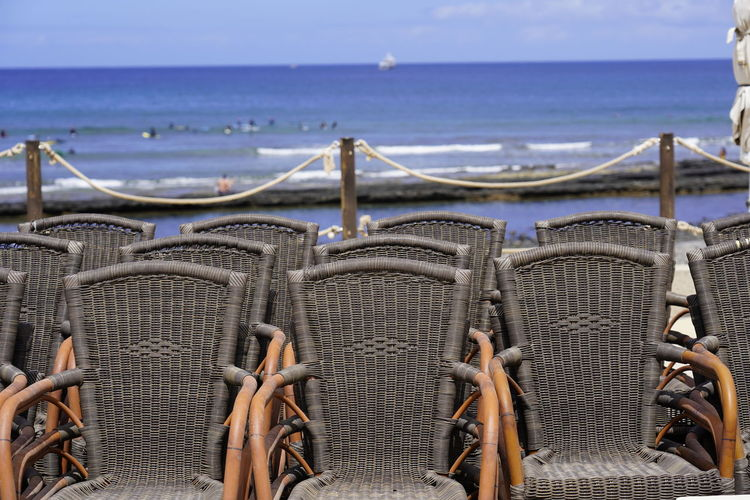Panoramic shot of chairs on beach against sky