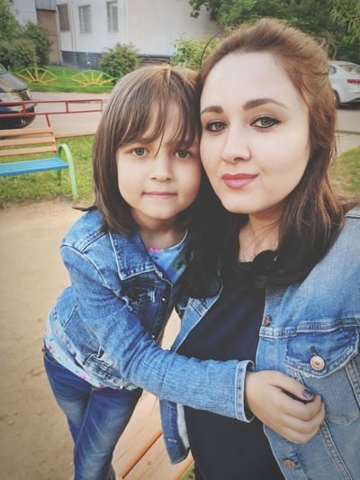 Portrait of woman with daughter in park