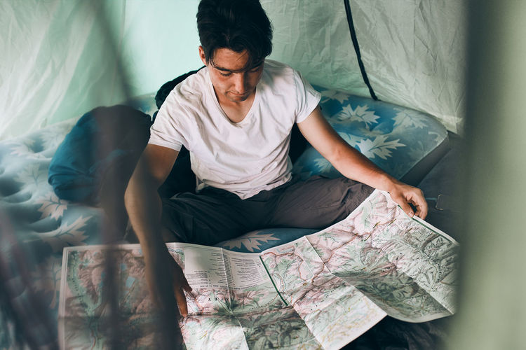 Young man looking at a map of mountain trails planning next trip on summer vacation