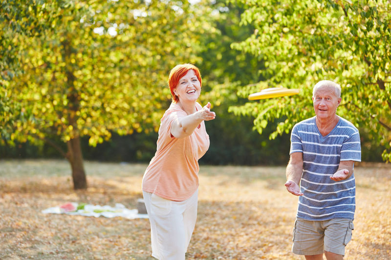 Smiling Couple Playing With Plastic Disc Against Trees