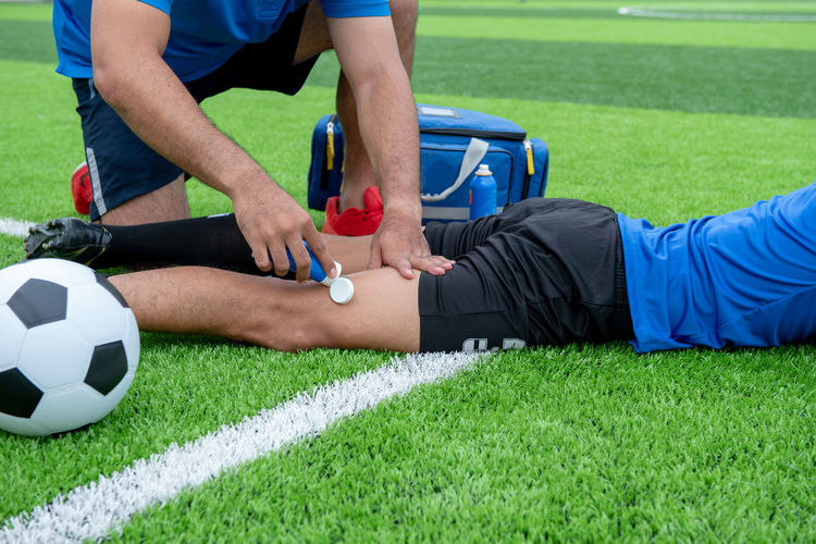 Low Section Of Male Physical Therapist Applying Ointment On Soccer Player Leg At Field