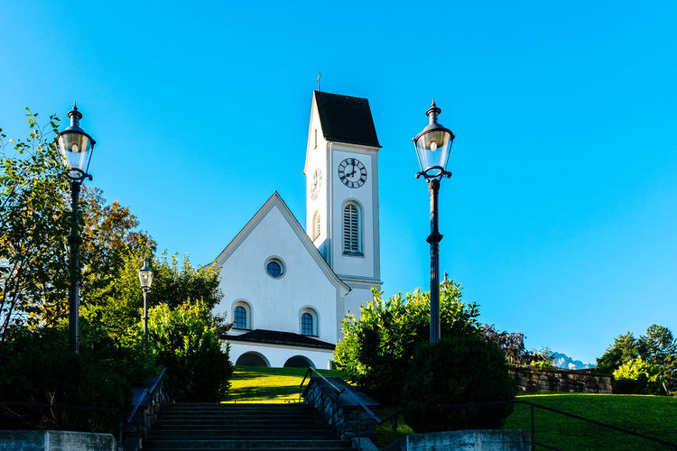 Architecture Bell Tower Blue Building Exterior Built Structure Chapel Church Clear Sky Day Façade Famous Place Green Color Kirche Kriens Kriens Lamp Post Low Angle View Outdoors Place Of Worship Religion Sky Staircase Stairs Steps Street Light Tree