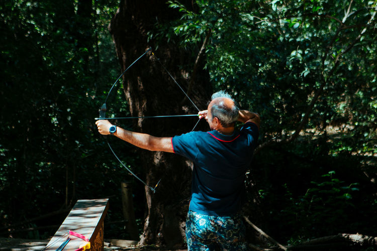 Full length of man holding bow in forest