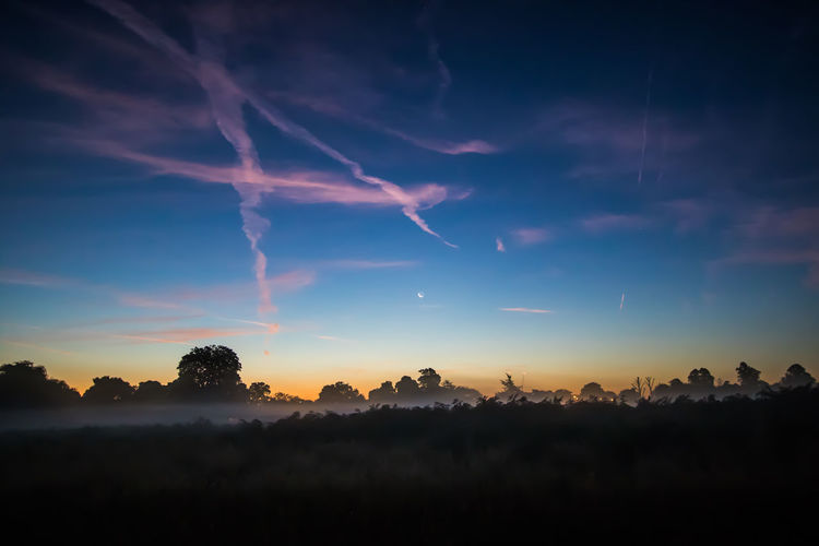 View of foggy field with clouds in blue sky at dusk