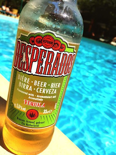 the pleasure of drinking a desperados on the edge of a pool Close-up Text Water Communication Western Script Freshness Focus On Foreground Blue Indulgence Outdoors No People