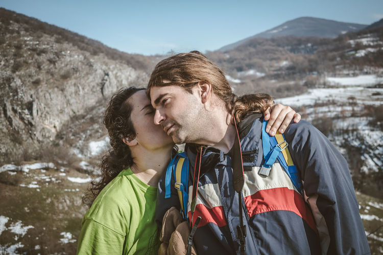 Woman kissing man while standing on mountains against sky