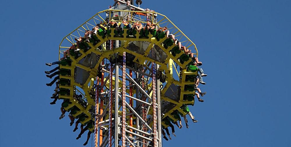 amusement park ride on the Münchener Oktoberfest Round About Amusement Park Ride Up And Down Rotation Blue Sky Low Angle View Amusement Park Built Structure Arts Culture And Entertainment Leisure Activity Sunlight Fun Enjoyment Excitement