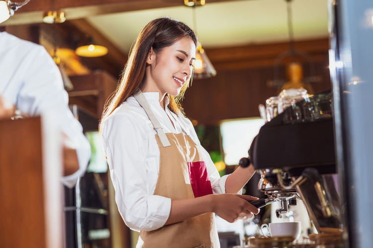 Young woman making coffee in cafe
