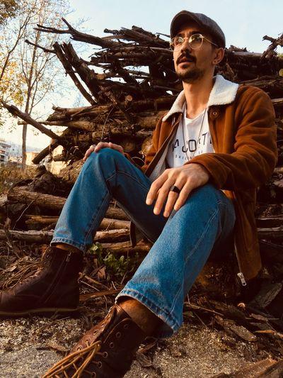 Full length of man sitting on logs