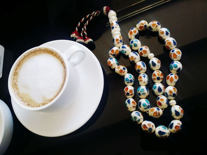 Close-Up Of Necklace By Coffee On Table