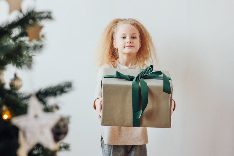 Portrait of a girl holding a christmas tree