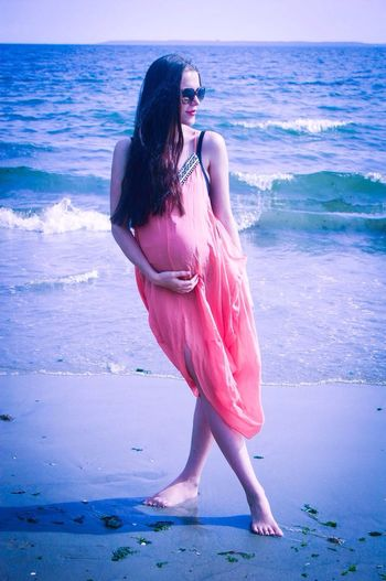 Full length of pregnant woman with legs crossed at knee standing at beach