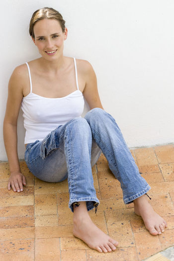 Portrait of smiling young woman sitting against wall