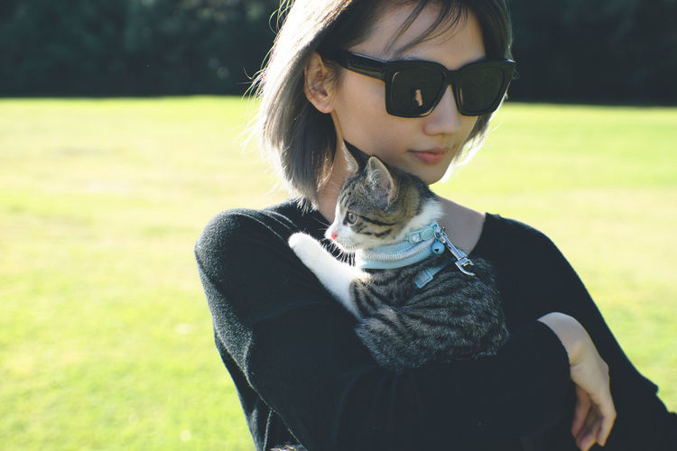 Woman wearing sunglasses while holding cat on field