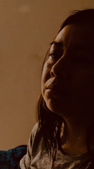 Close-up of sad woman sitting at home