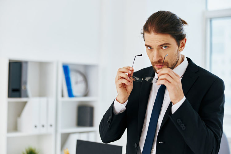 Young man holding camera in office