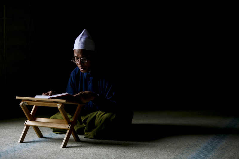 Man Reading In Koran In Mosque