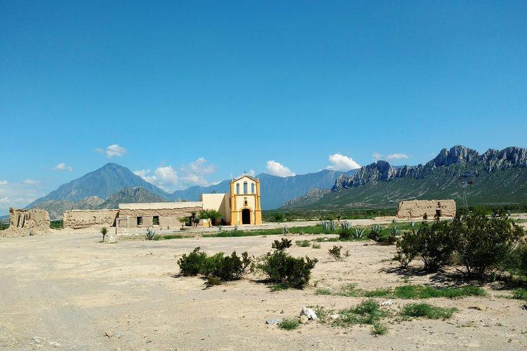 Church On Landscape Against Mountain Range