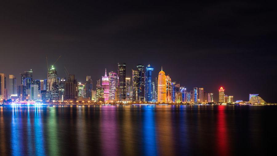 Illuminated city by bay against sky at night