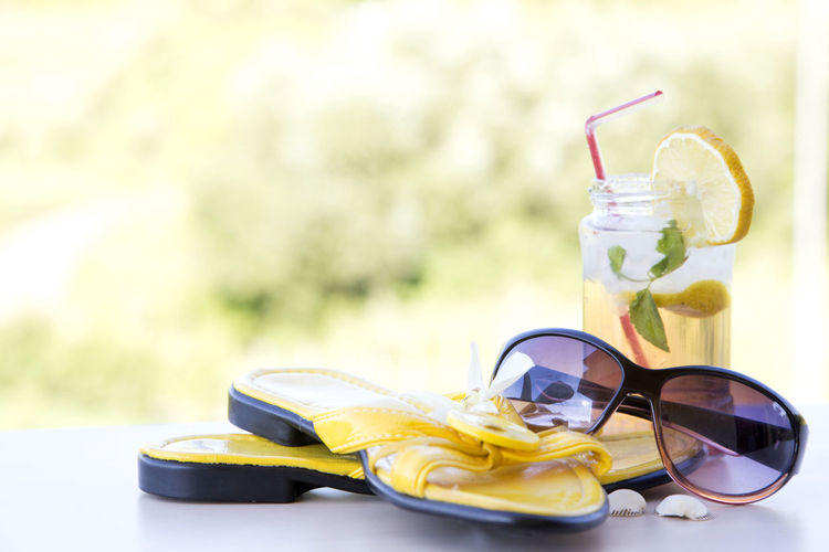 Close-up of sunglasses slippers and drink on table