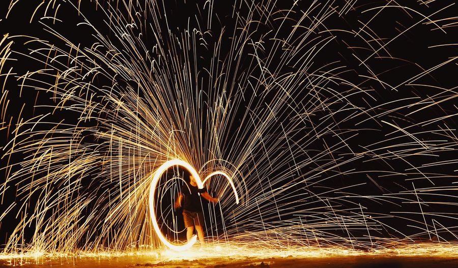 Man spinning lit wire wool at night