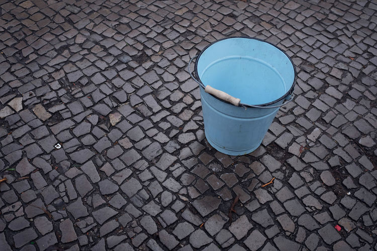 High angle view of bucket on cobblestone street