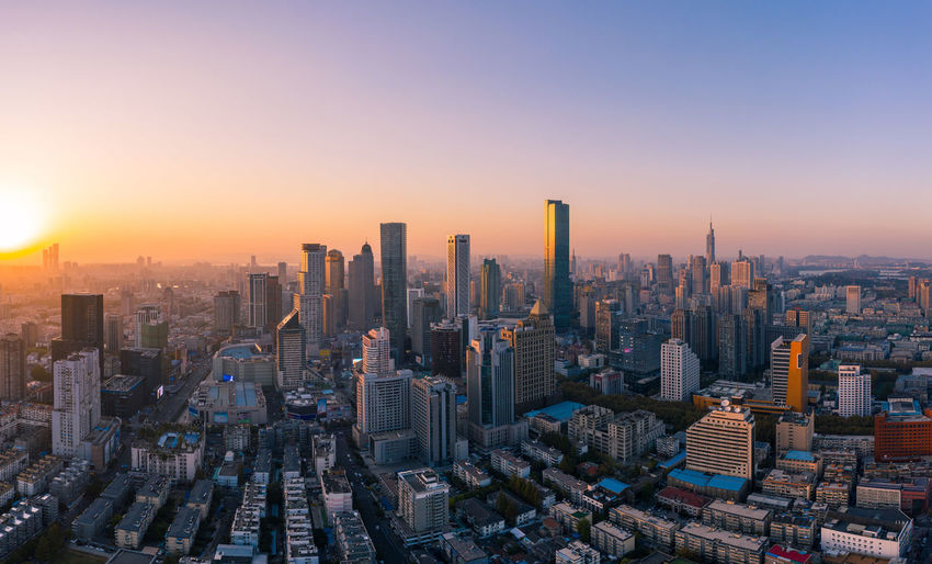 Aerial view of modern buildings in city against sky during sunset