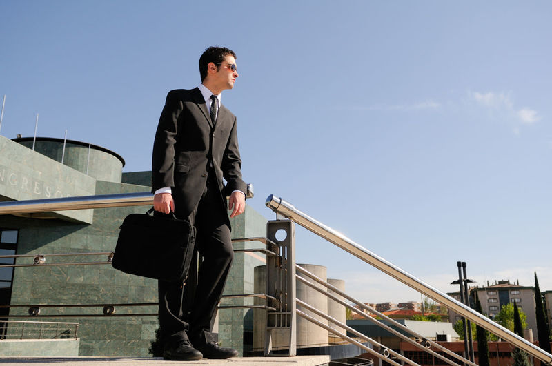 Low angle view of businessman standing against blue sky